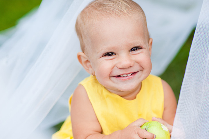 A child holding an apple and smiling