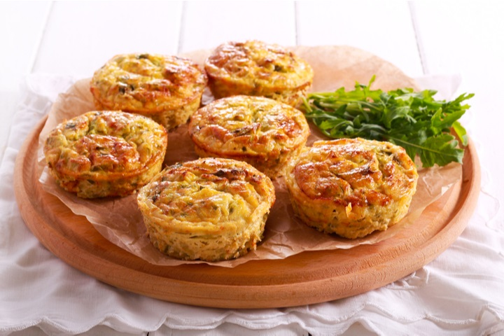 courgette-frittatas-on-wooden-board-table-720851998